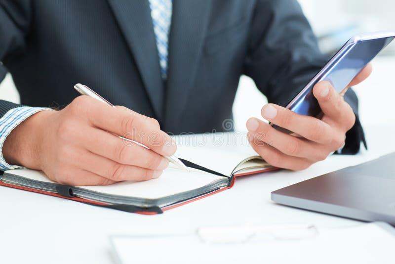 Homem de negócios no terno preto usando o telefone esperto móvel e trabalhando no fim do laptop acima Apenas handss das mãos sobr fotografia de stock