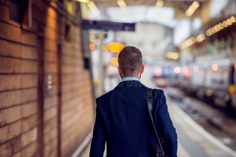 Homem de negócios no terno que anda no staition, vista traseira imagem de stock