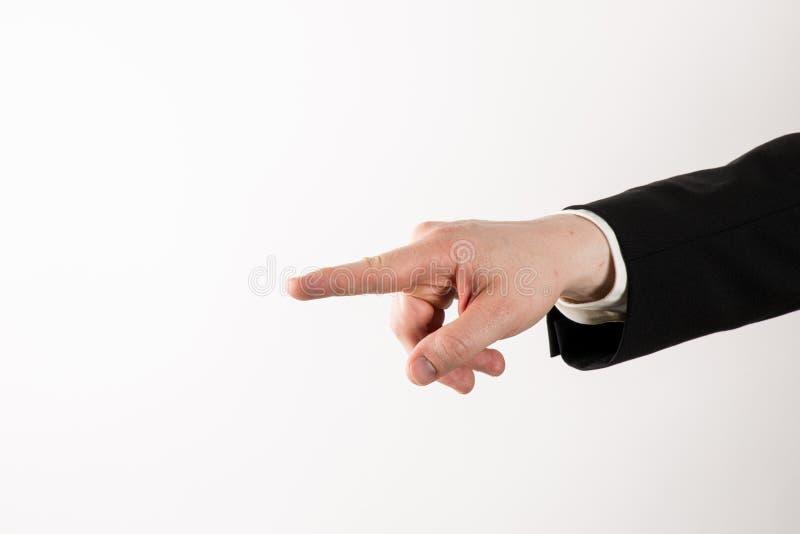Homem de negócios no terno que aponta em você ou em mostrar imagem de stock