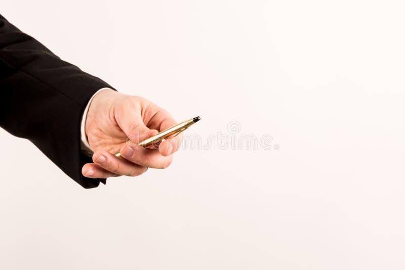 Homem de negócios no terno que dá uma pena dourada a você fotografia de stock