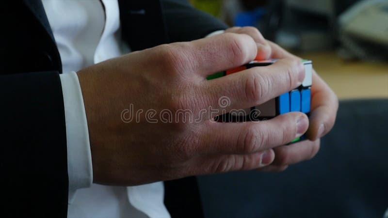Homem de negócios no terno que guarda o cubo do ` s de Rubik Homem de negócios que tenta montar um close up do cubo do ` s de Rub foto de stock