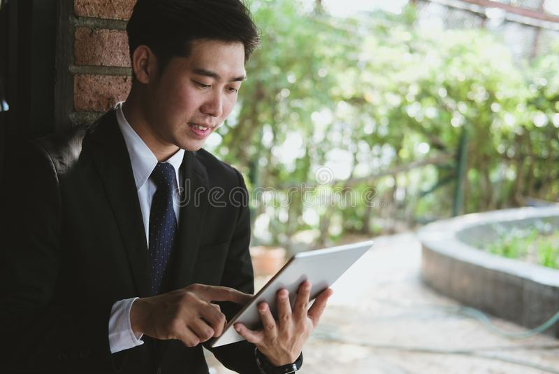 Homem de negócios no terno que guarda o touchpad ao estar o buil exterior imagens de stock royalty free