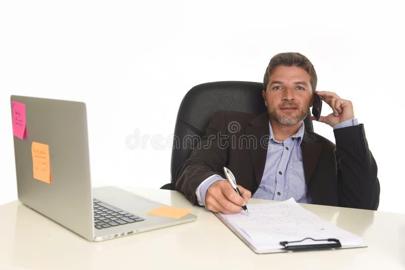 Homem de negócios no terno que trabalha na mesa do laptop que fala no telefone celular no escritório moderno foto de stock