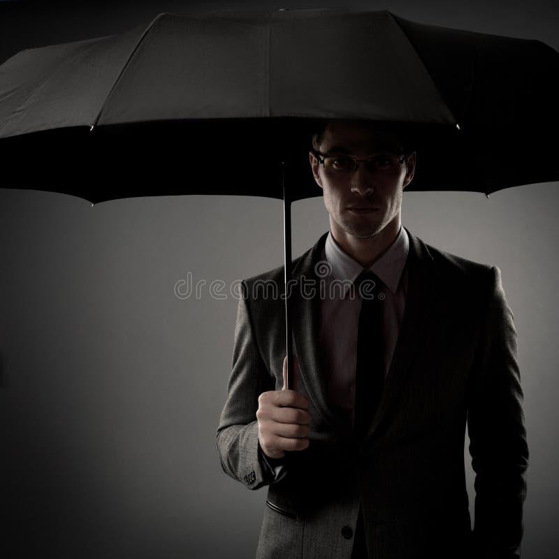 Homem de negócios no traje que prende o guarda-chuva preto foto de stock