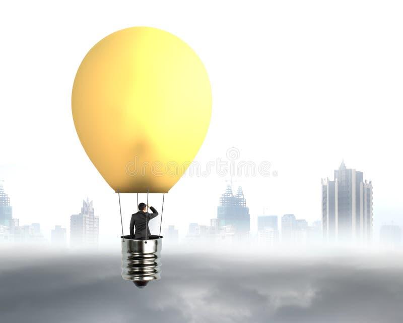 Homem de negócios no voo brilhantemente amarelo do balão de ar quente da lâmpada foto de stock royalty free
