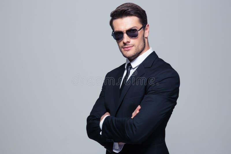 Homem de negócios nos óculos de sol que estão com os braços dobrados imagens de stock