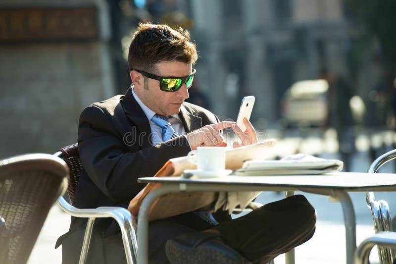 Homem de negócios nos óculos de sol que têm o jornal da leitura do café do café da manhã usando o Internet no telefone celular fotografia de stock