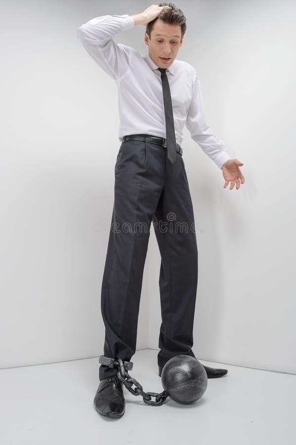 Homem de negócios nos grilhões. Comprimento completo do olhar chocado do homem de negócios imagens de stock