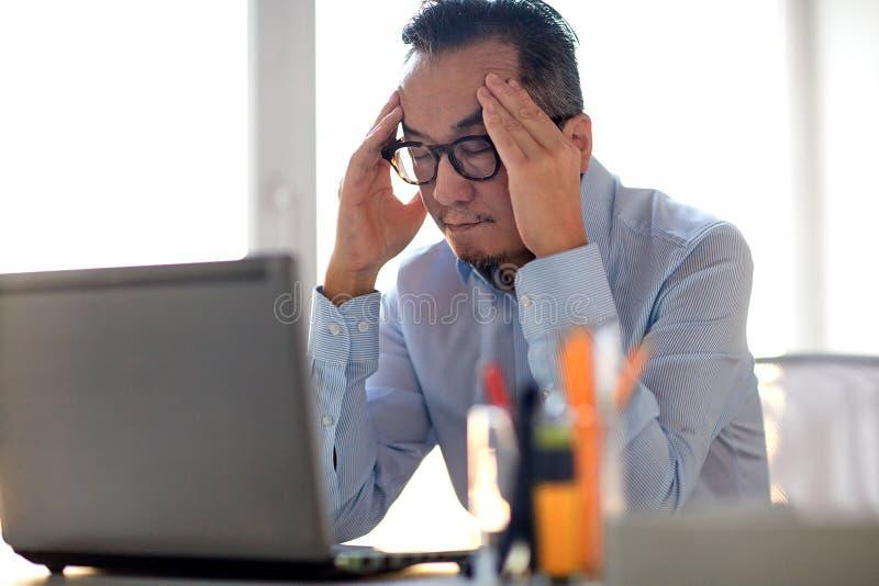 Homem de negócios nos monóculos com o portátil no escritório imagem de stock royalty free
