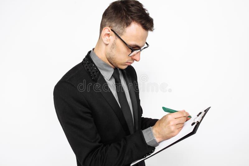 Homem de negócios nos vidros e terno que guarda uma folha de papel vazia, foto de stock