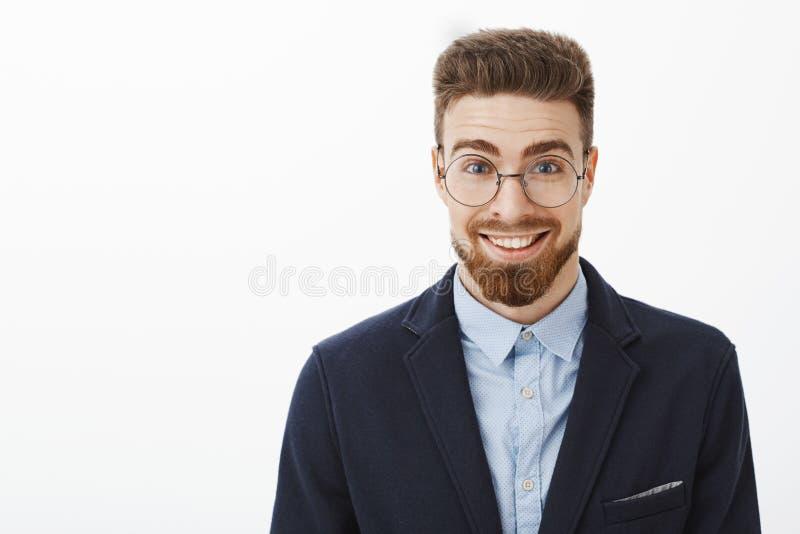 Homem de negócios novo à moda esperto e criativo ambicioso em vidros redondos com barba e em olhos azuis que estão no terno na mo imagens de stock royalty free