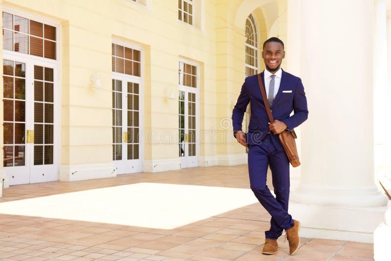 Homem de negócios novo amigável que está construindo fotografia de stock royalty free