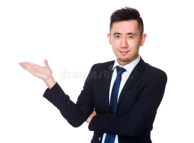 Homem de negócios novo asiático com a palma aberta da mão imagem de stock