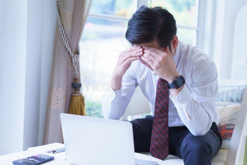 Homem de negócios novo asiático forçado que trabalha com portátil e que guarda principal com as mãos que olham para baixo imagem de stock
