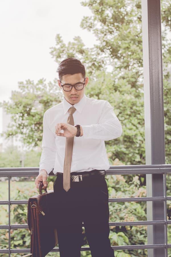Homem de negócios novo asiático Olhando o relógio de ponto, as reuniões da espera os processos do anúncio publicitário envolvidos fotografia de stock royalty free