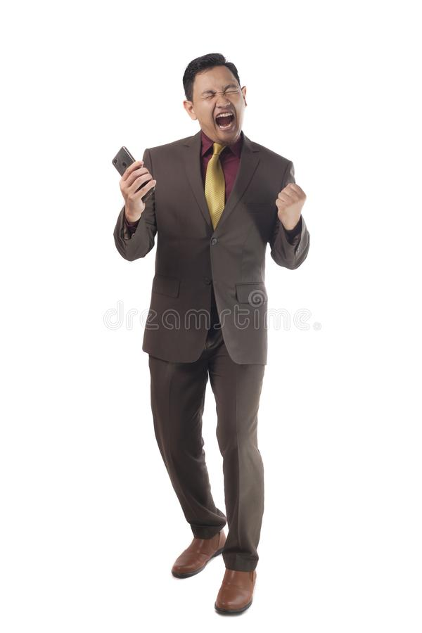 Homem de negócios novo atrativo para receber más notícias em seu telefone, gesto gritando irritado fotos de stock