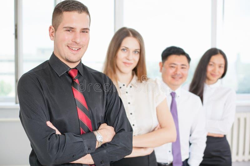 Homem de negócios novo bem sucedido e sua equipe do negócio imagem de stock royalty free