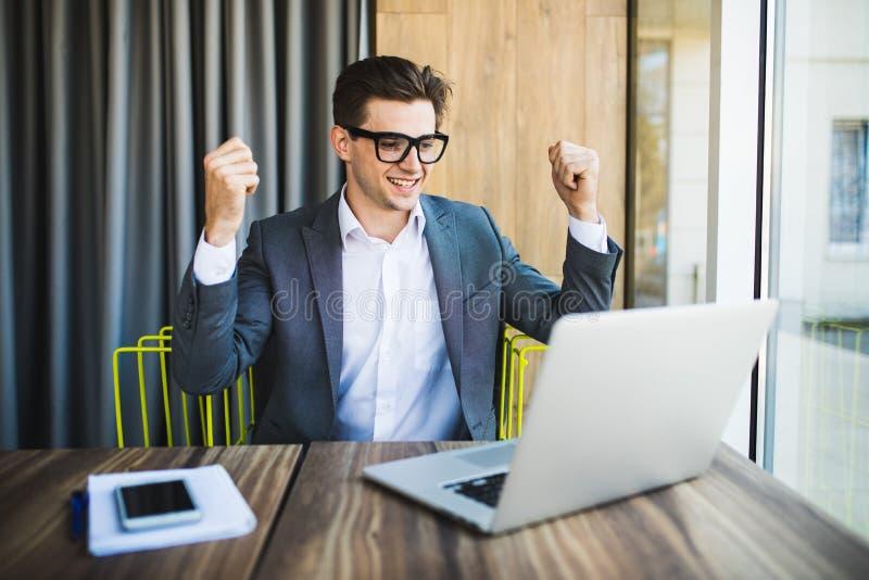 Homem de negócios novo bem sucedido que aprecia o sucesso em sua mesa vitória foto de stock royalty free