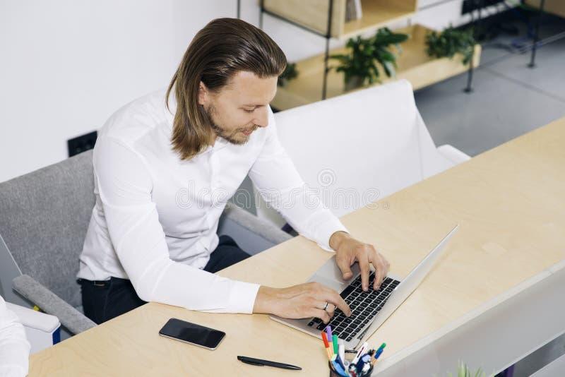 Homem de negócios novo bem sucedido que datilografa no portátil no local de trabalho fotografia de stock royalty free