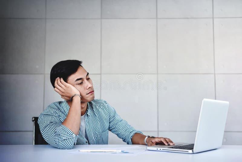 Homem de negócios novo cansado e forçado Sitting na mesa no escritório com portátil do computador Homem esgotado fotos de stock