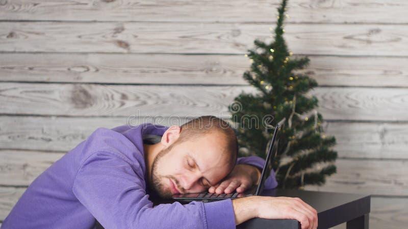 Homem de negócios novo cansado no escritório na véspera de ano novo Árvore de Natal no escritório Portátil na mesa Conceito do ne foto de stock