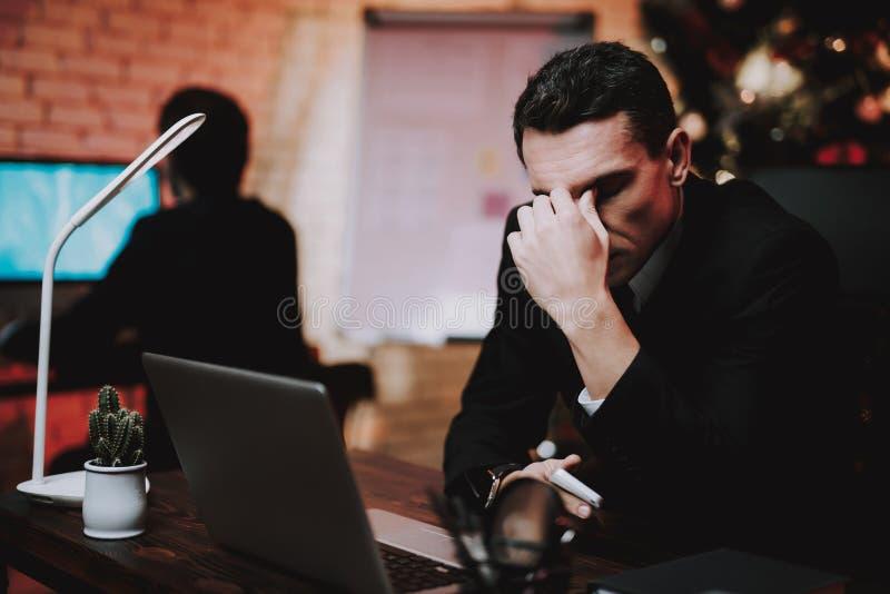 Homem de negócios novo cansado no escritório na véspera de ano novo fotografia de stock