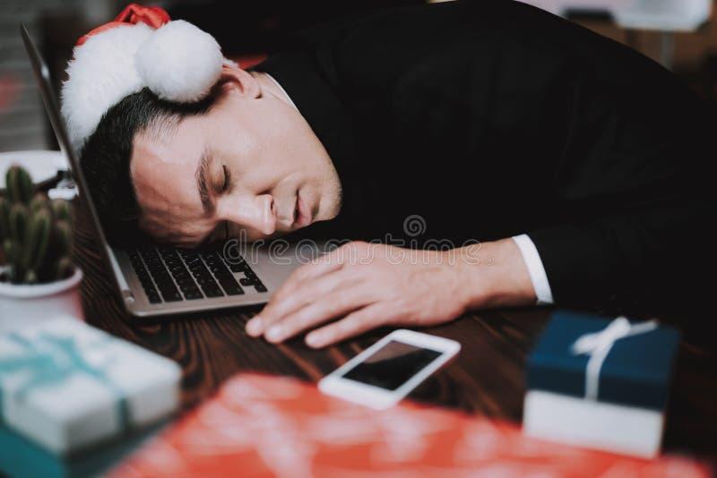 Homem de negócios novo cansado no escritório na véspera de ano novo fotografia de stock royalty free