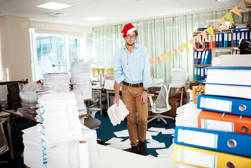 Homem de negócios novo cansado que trabalha no escritório entre papéis no dia de Natal fotografia de stock royalty free