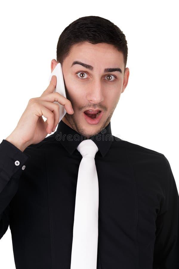 Homem de negócios novo com expressão surpreendida no telefone imagem de stock