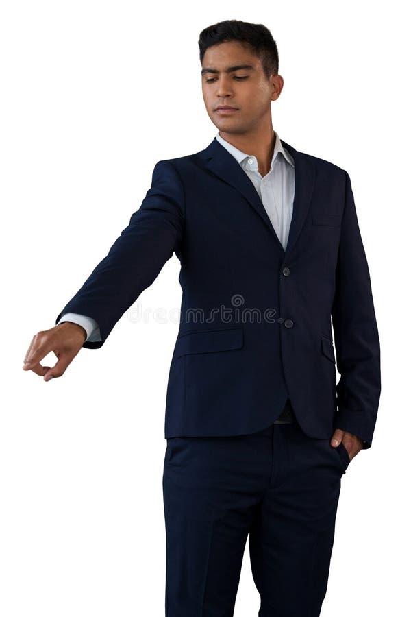 Homem de negócios novo com mãos em relação invisível tocante dos bolsos foto de stock