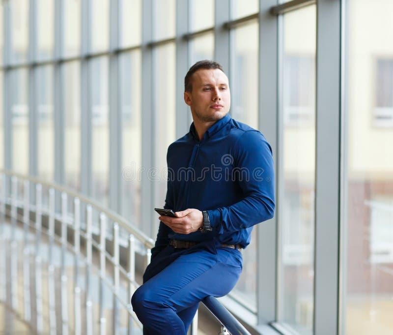 Homem de negócios novo com o telefone celular na sala de estar do aeroporto fotografia de stock