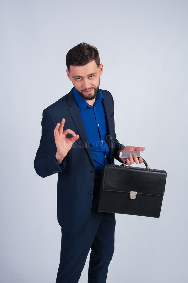 Homem de negócios novo com o telefone e a pasta que mostram está bem imagem de stock royalty free