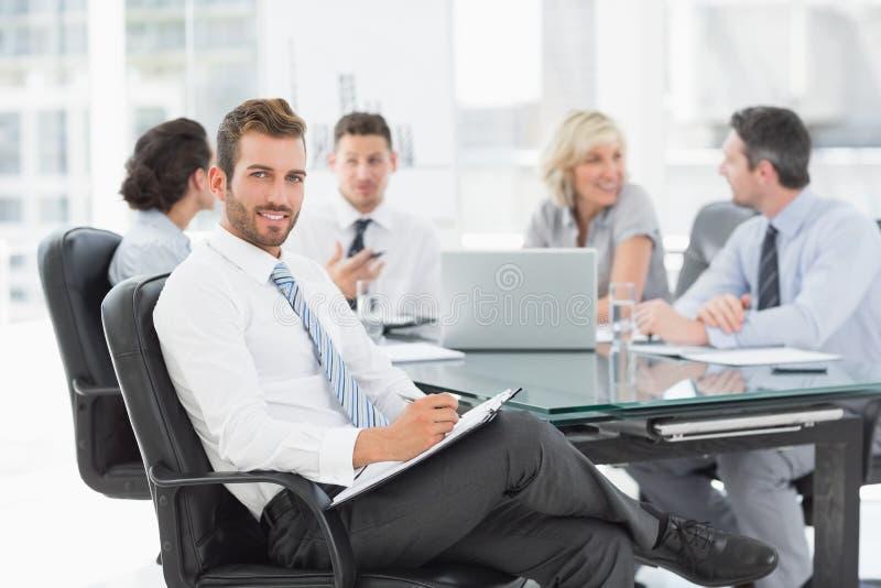 Homem de negócios novo com os colegas que discutem no escritório imagens de stock