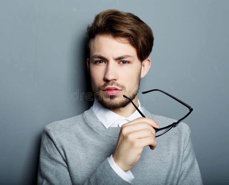 Homem de negócios novo com os monóculos, olhando a câmera contra imagens de stock