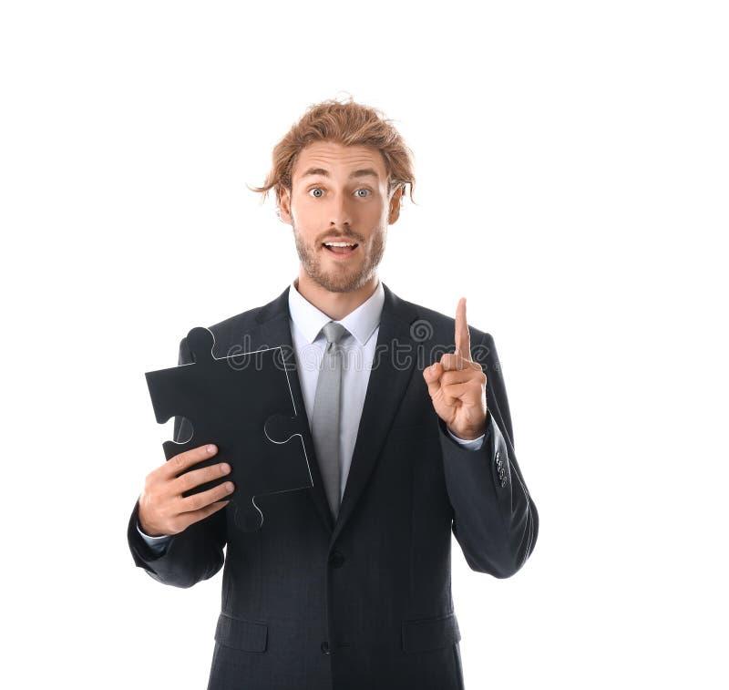 Homem de negócios novo com parte de enigma de serra de vaivém e o indicador aumentado no fundo branco imagem de stock