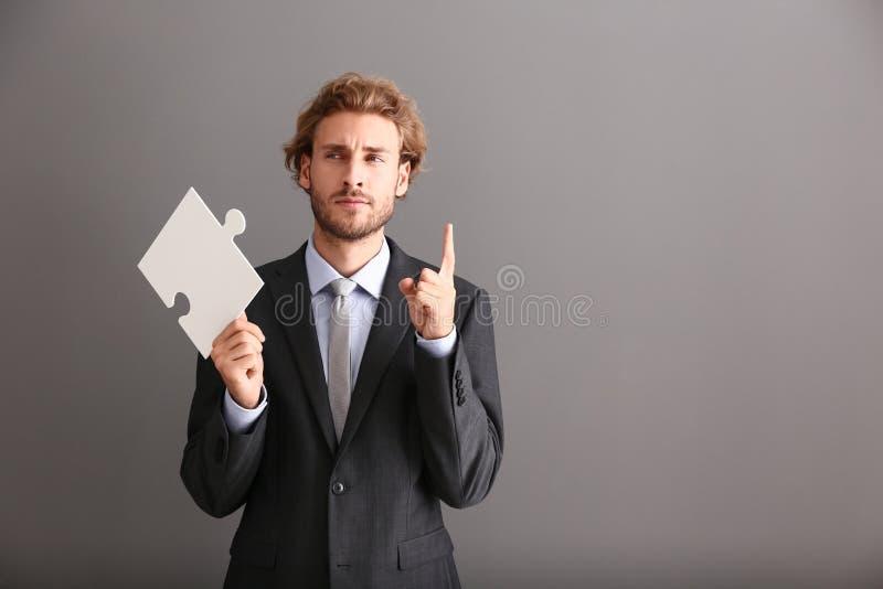 Homem de negócios novo com parte de enigma de serra de vaivém e o indicador aumentado no fundo cinzento imagem de stock royalty free