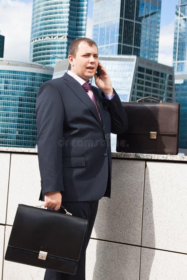 Homem de negócios novo com pasta que fala no telefone fotos de stock royalty free