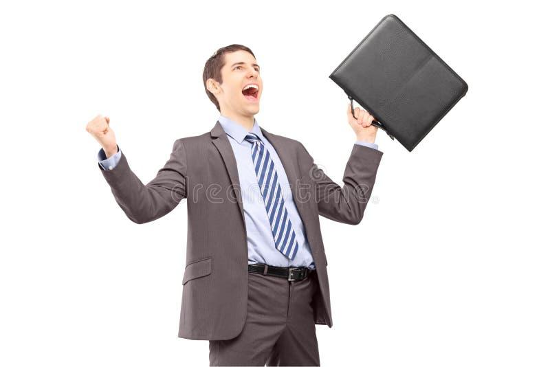 Homem de negócios novo com pasta que gesticula o excitamento com aumento