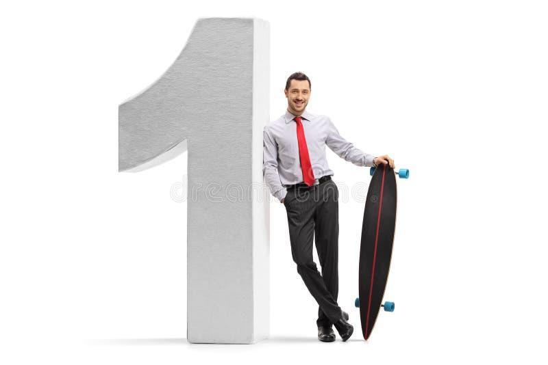 Homem de negócios novo com um longboard que inclina-se contra um número um fotos de stock