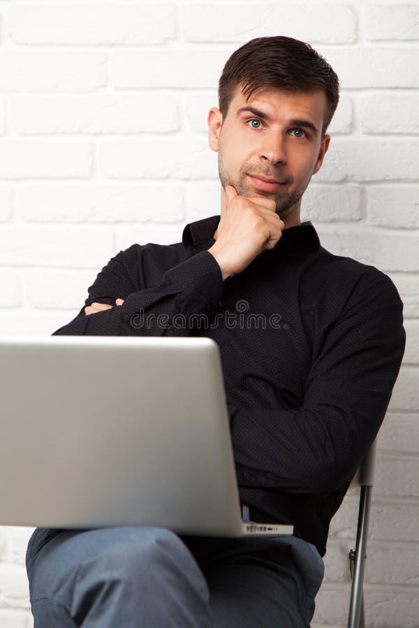 Homem de negócios novo com um portátil imagem de stock