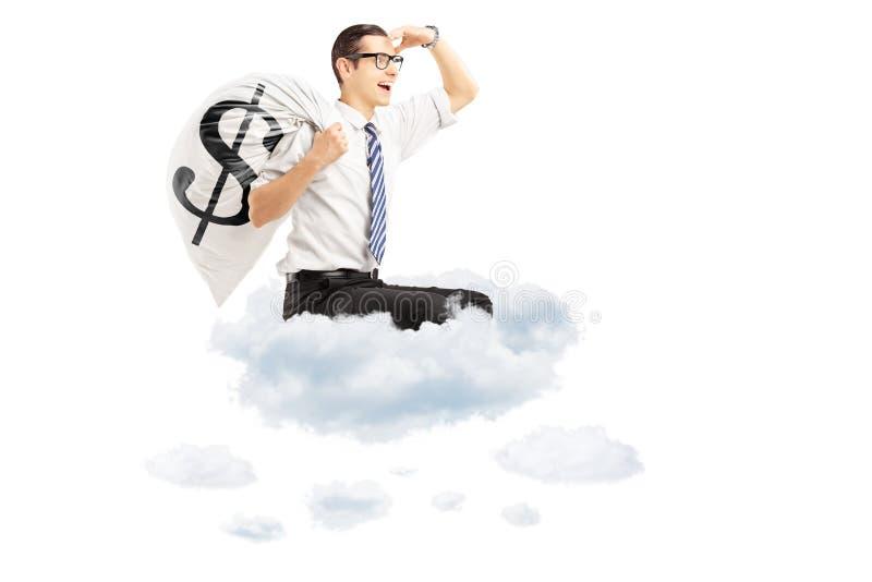 Homem de negócios novo com um voo do saco do dinheiro em nuvens fotografia de stock