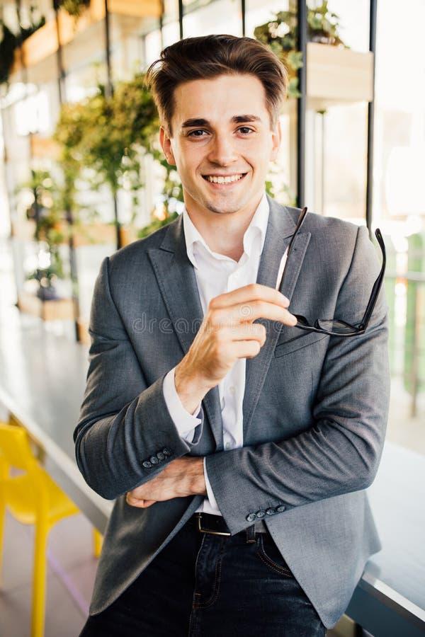 Homem de negócios novo com vidros em seus braços que sentam-se na borda de sua mesa de madeira que olha seriamente na câmera fotografia de stock royalty free