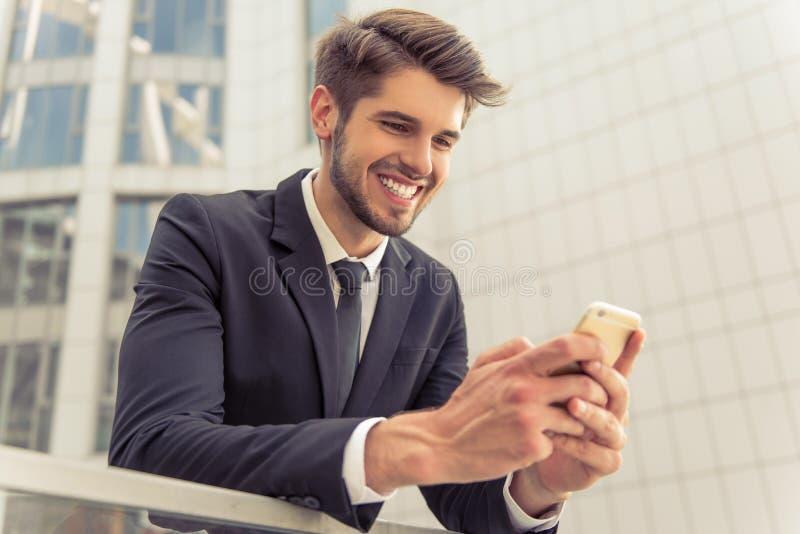 Homem de negócios novo considerável com dispositivo foto de stock