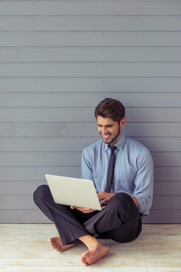 Homem de negócios novo considerável com dispositivo imagens de stock