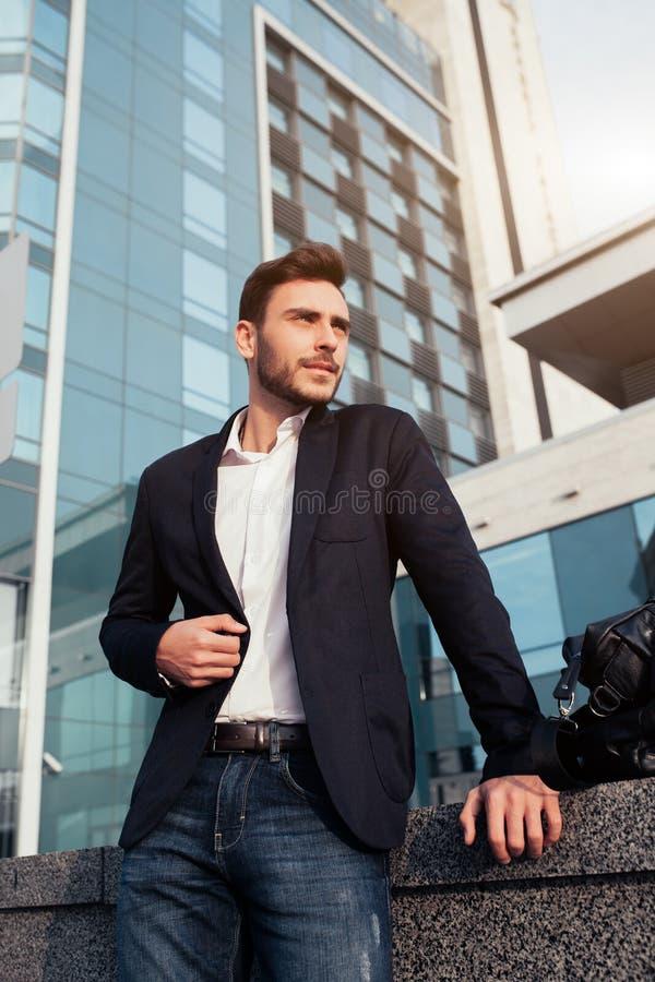 Homem de negócios novo considerável com uma barba e em uma posição do terno de negócio na rua na perspectiva do escritório imagens de stock
