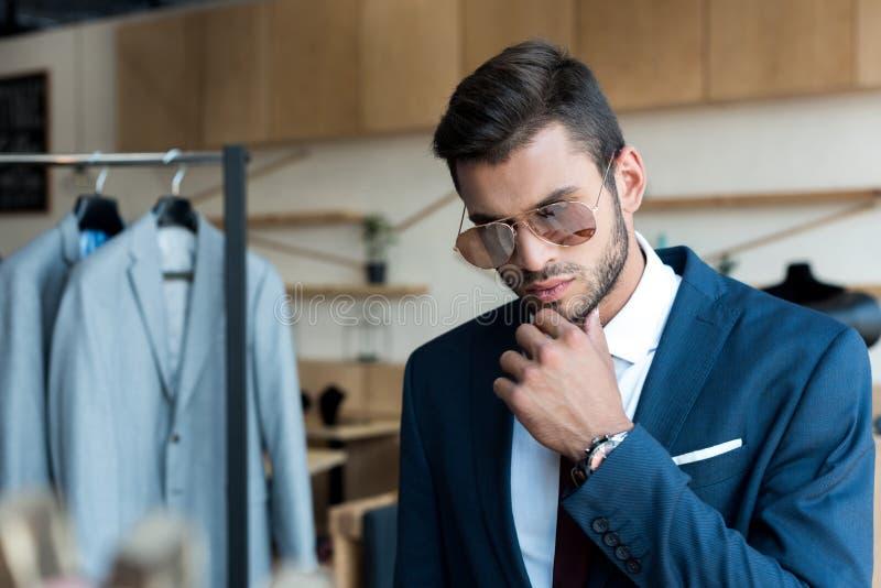 homem de negócios novo considerável em estar dos óculos de sol imagens de stock