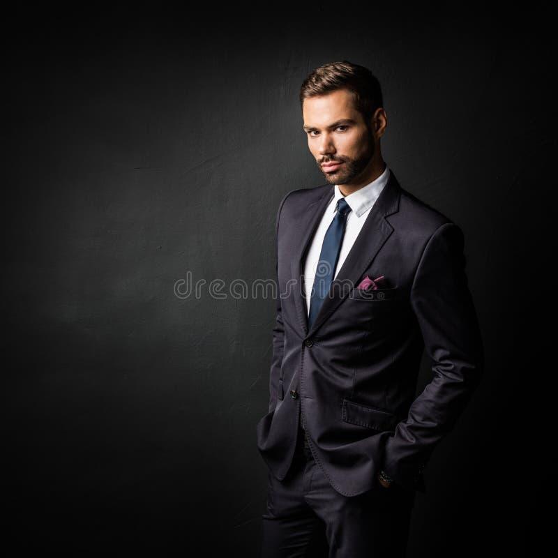 Homem de negócios novo considerável que está seguro no preto fotos de stock royalty free