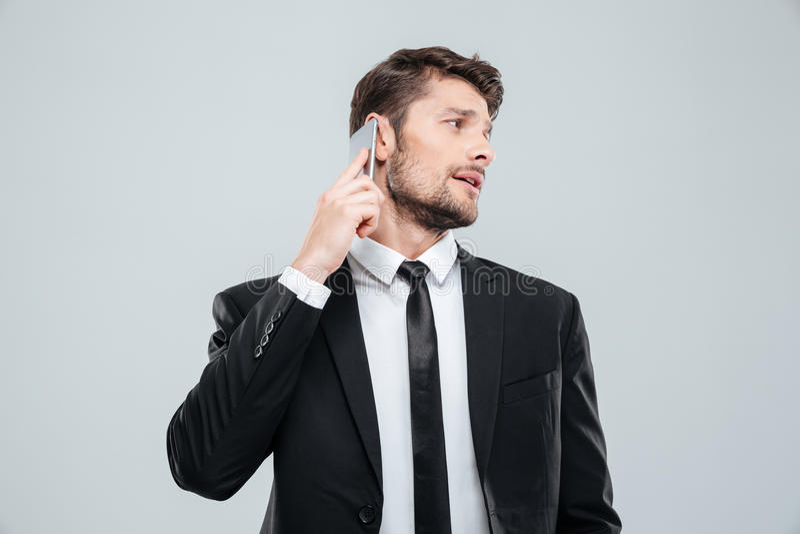 Homem de negócios novo considerável que fala no telefone celular e que olha para trás fotografia de stock royalty free