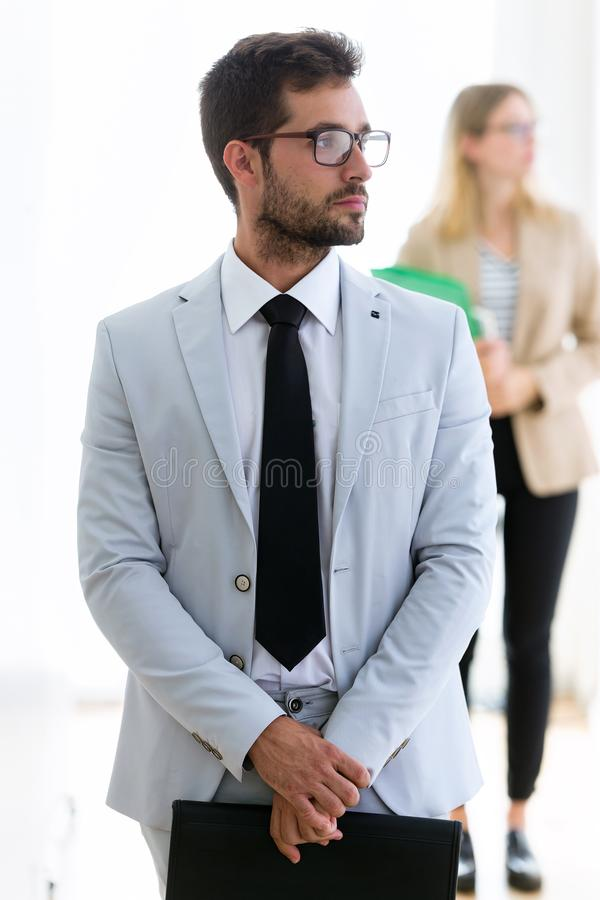 Homem de negócios novo considerável que olha lateralmente com seu sócio atrás em um corredor dos eles empresa fotografia de stock royalty free