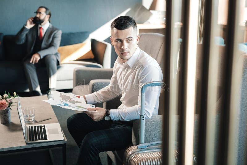 Homem de negócios novo considerável que senta-se no funcionamento da poltrona duramente imagens de stock royalty free